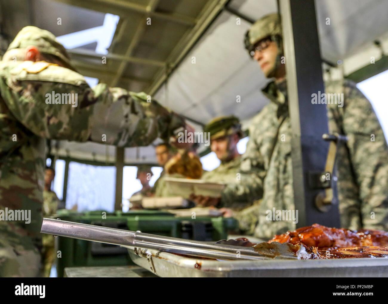 Les soldats se déplacent à travers la gamme de nourriture du petit déjeuner dans une cuisine recevez le trailer mis en place dans le domaine, Camp Ripley, Minn., 15 août 2018. Les cuisines sont en mesure de faire cuire la nourriture et le service des repas en cours de l'installation dans une seule journée. (U.S. Réserve de l'armée photo prise par le s.. Adam Decker) Photo Stock