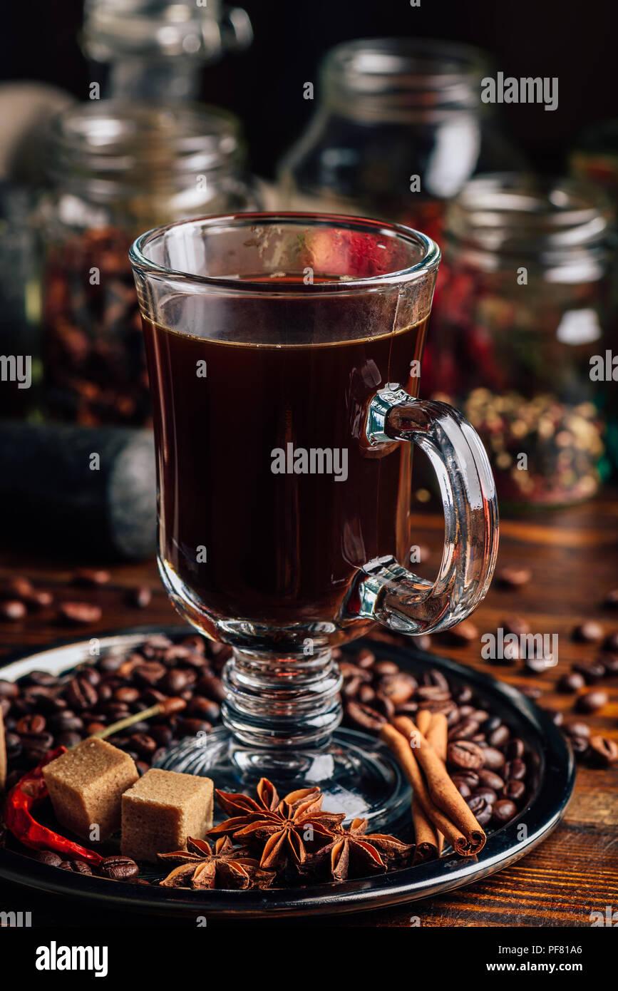 Tasse de café sur la plaque de métal avec des haricots, du sucre raffiné et le bâton de cannelle, d'anis et de piment. Photo Stock