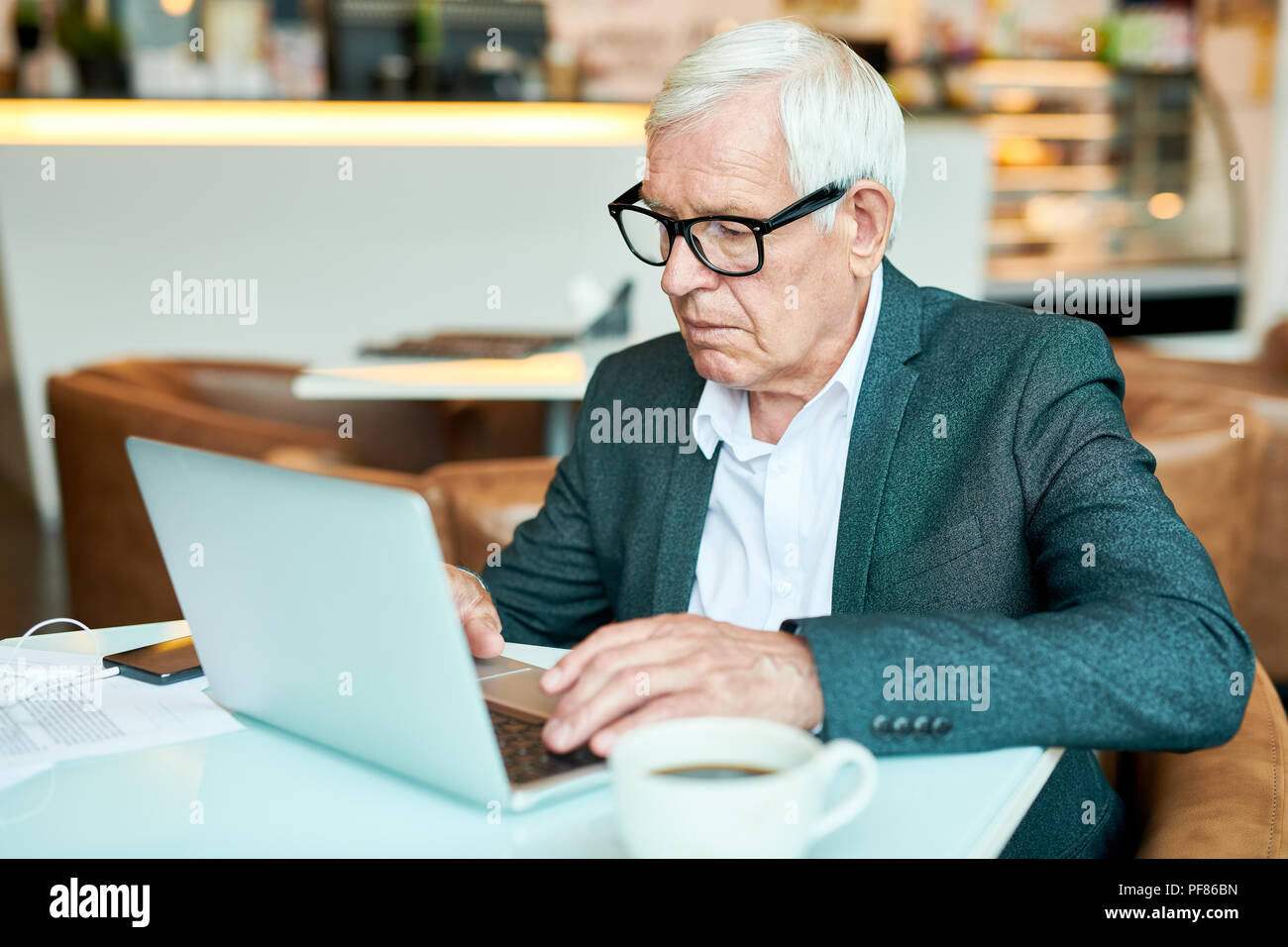 Senior Businessman Using Laptop in Cafe Photo Stock