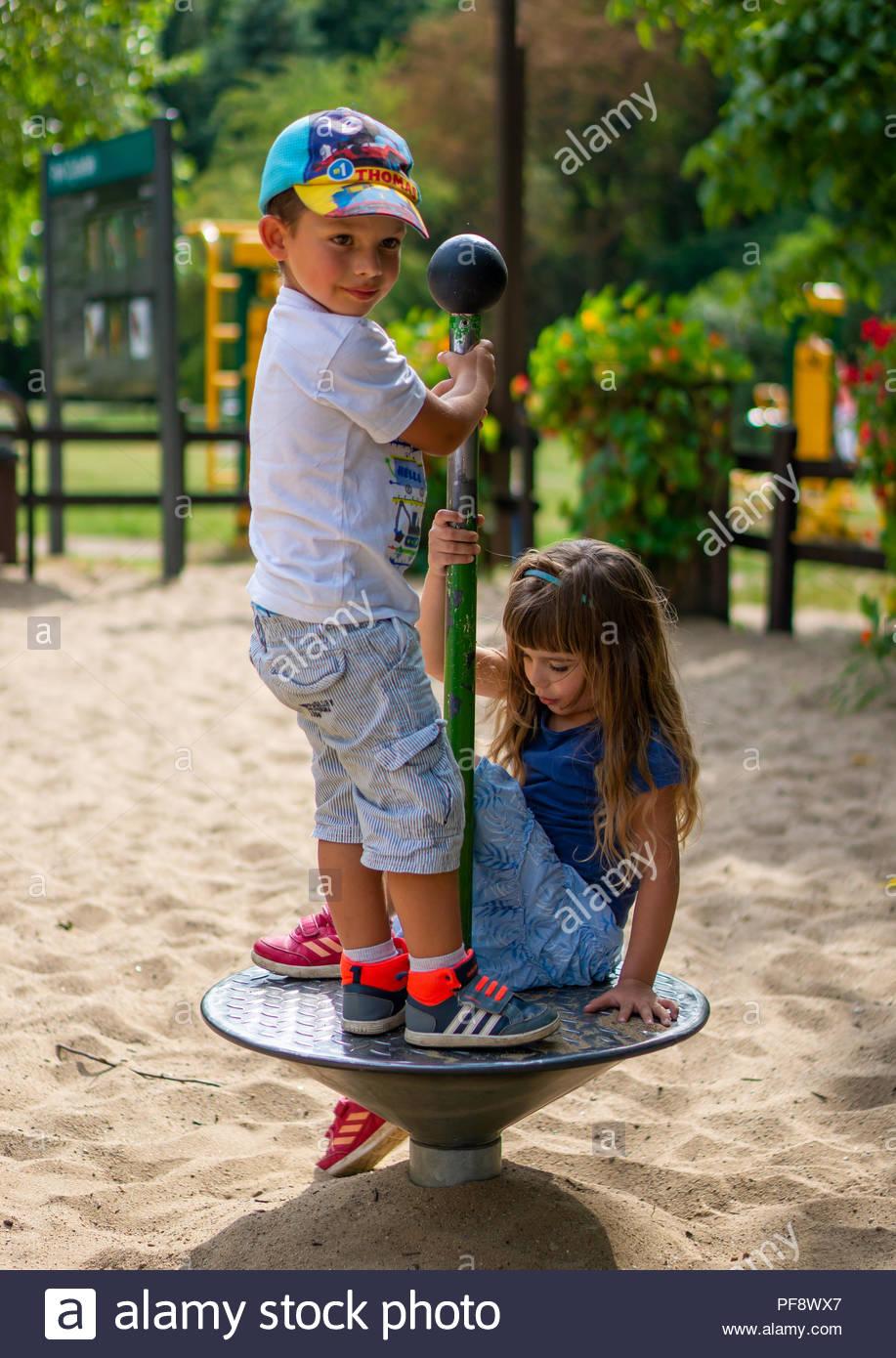 Jeune garçon et fille avec de longs cheveux sur un équipement de spin dans un terrain sur le parc Cytadela à Poznan, Pologne Banque D'Images