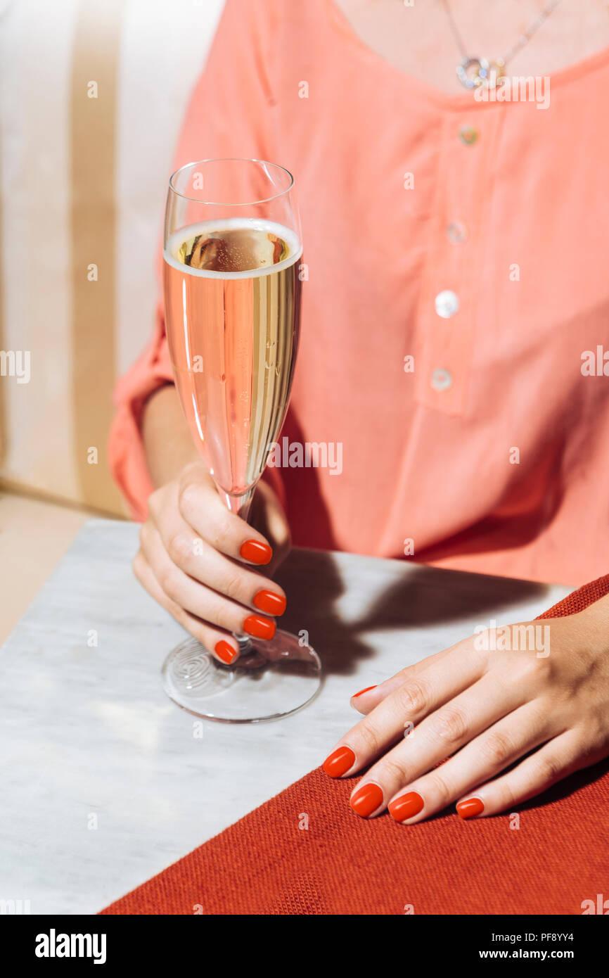 Un verre de prosecco tenu par une fille dans un bar élégant avec des couleurs pop vintage Photo Stock