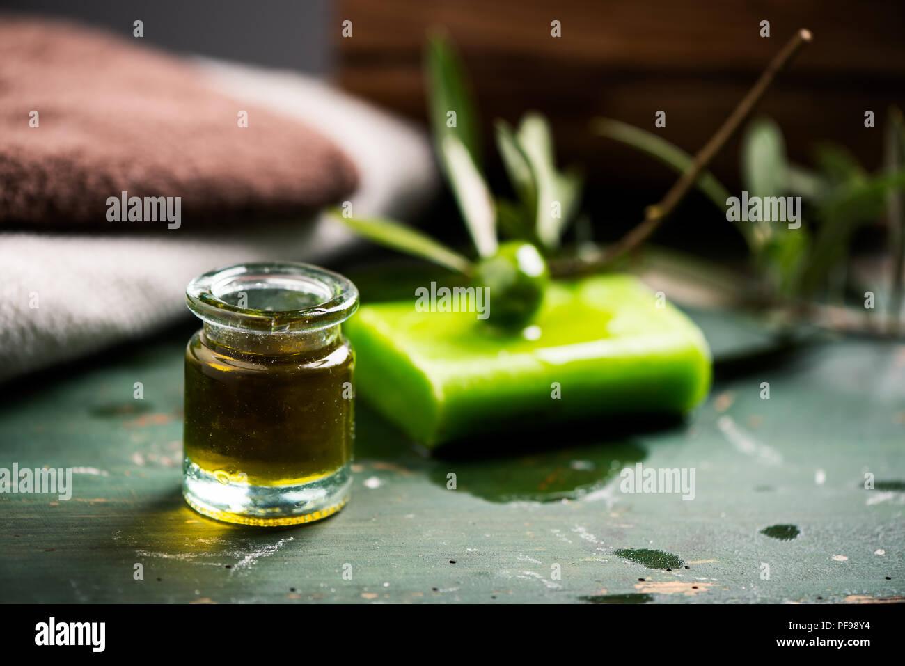 Natural spa avec de l'huile d'olive savon en barre et serviettes onn un bois vert table vinatge Photo Stock