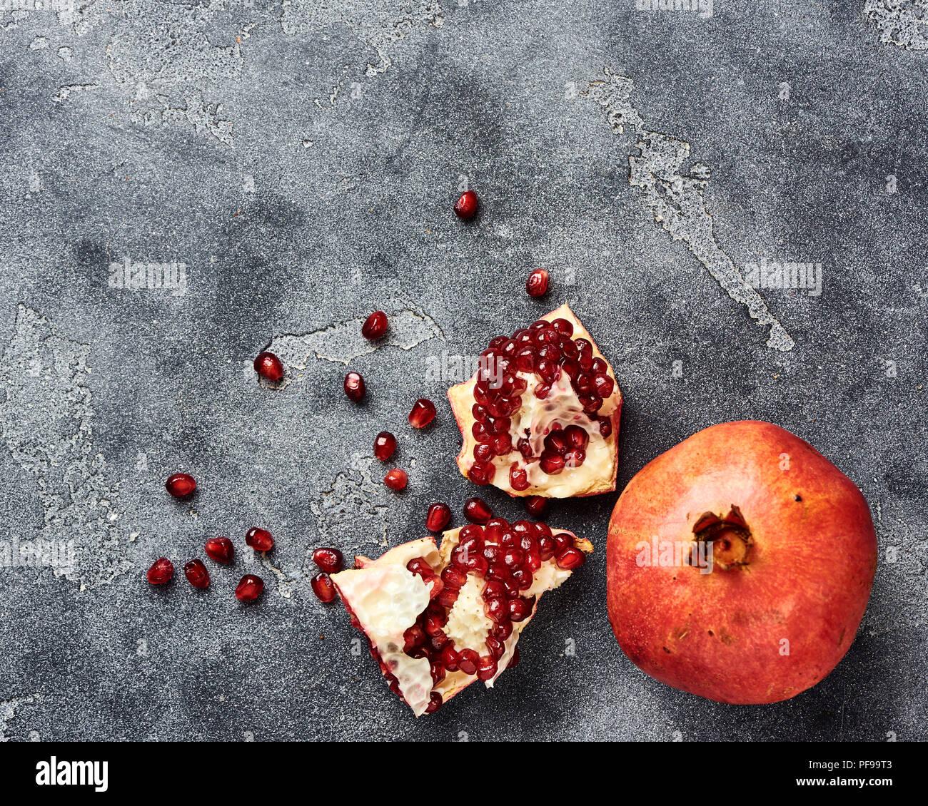 Fruits avec graines de grenade sur fond gris avec copie espace. Vue d'en haut. Photo Stock