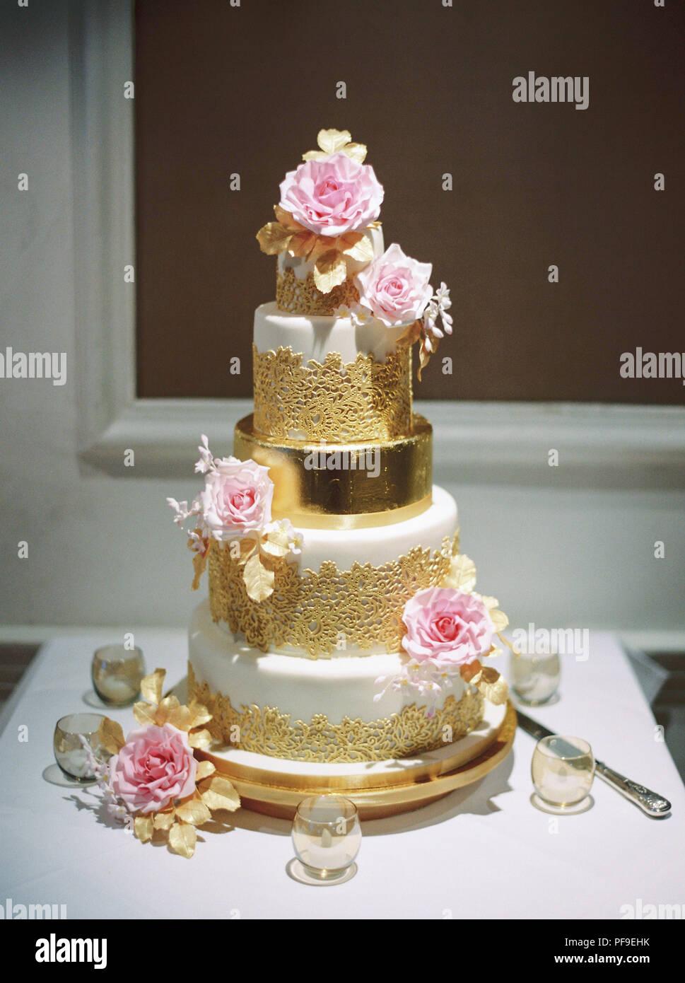 L'or blanc rose tiered gâteau de mariage avec des roses Photo Stock
