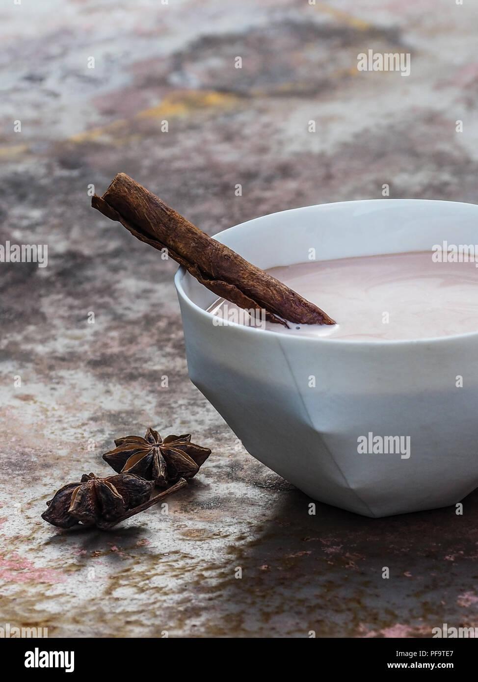 Thé chai latte fait maison avec le bâton de cannelle. Photo Stock