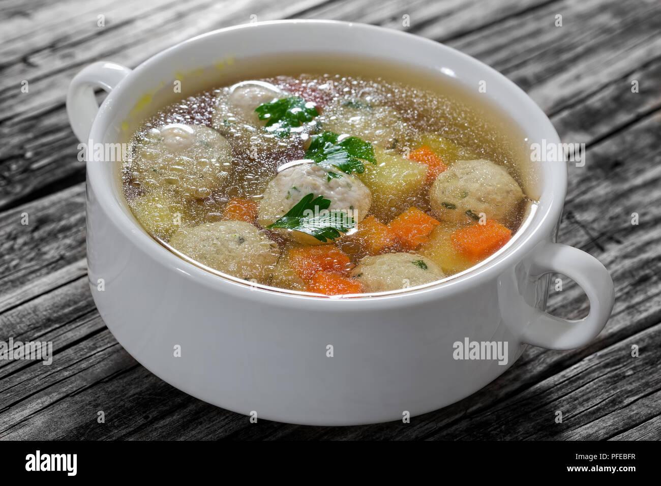 Délicieux produits biologiques soupe au poulet avec des boulettes de viande, les carottes et les pommes de terre saupoudrées de persil dans le bol de soupe traitée deux fois sur la vieille table en bois, close-up Banque D'Images