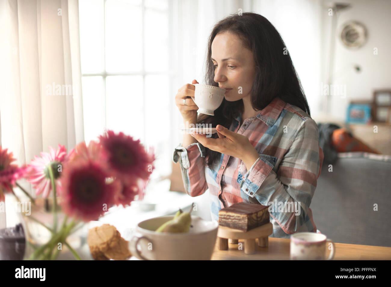 Femme avec une tasse de café, un bon matin à la maison. Le petit-déjeuner et café parfumé. L'intérieur est confortable et les fleurs. Espace libre pour le texte. Photo Stock