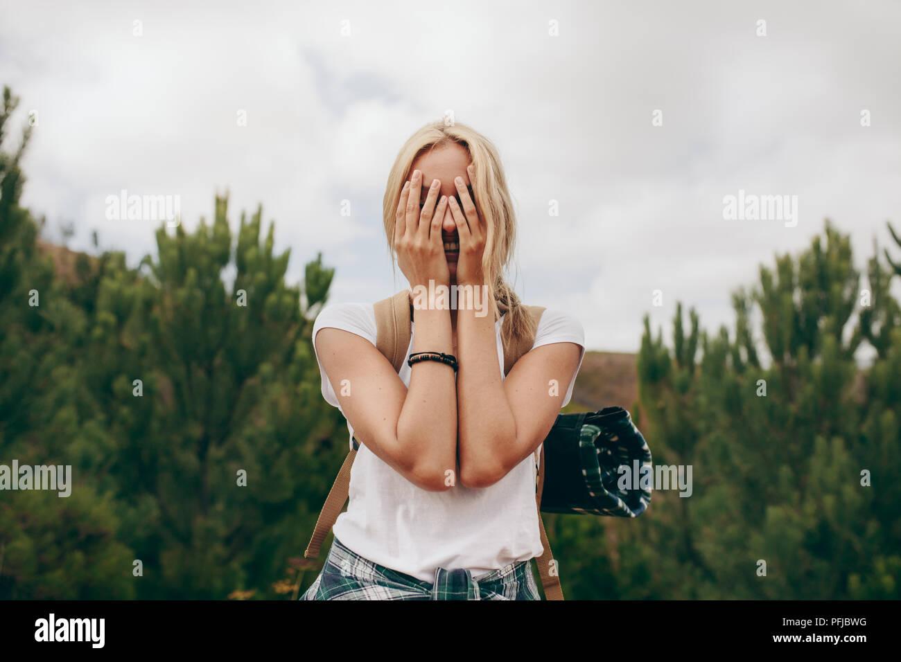 Voyageuses couvrant son visage avec les mains debout dans une forêt. Maison de vacances sur une femme portant un sac de voyage. Photo Stock
