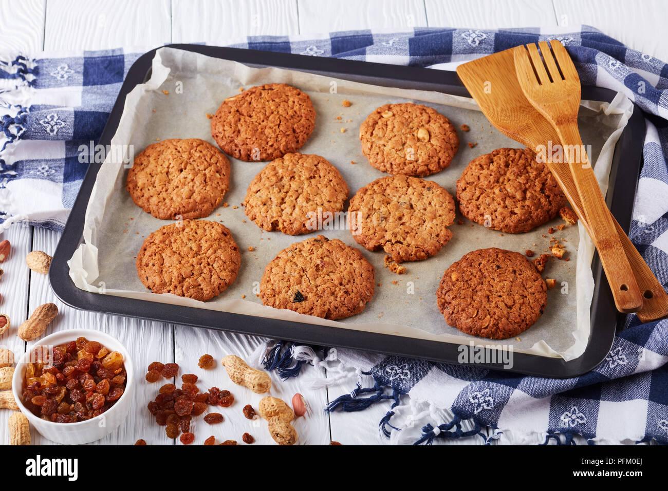Biscuits fraîchement cuits au four avec des raisins secs et les arachides sur une plaque de cuisson avec des spatules en bois et cuisine serviette, vue horizontale à partir de ci-dessus, close-up Banque D'Images