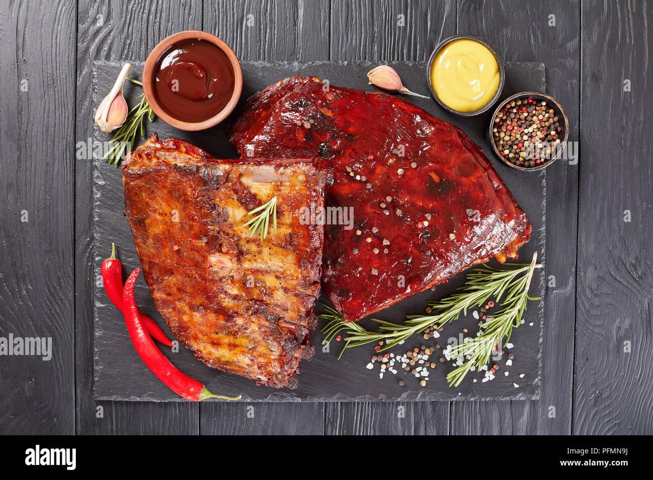 Juteux délicieux barbecue fumé maison côtes levées de porc sur la plaque en pierre noire avec des épices, du romarin frais, de la moutarde et de la sauce barbecue, vue verticale d'un Banque D'Images