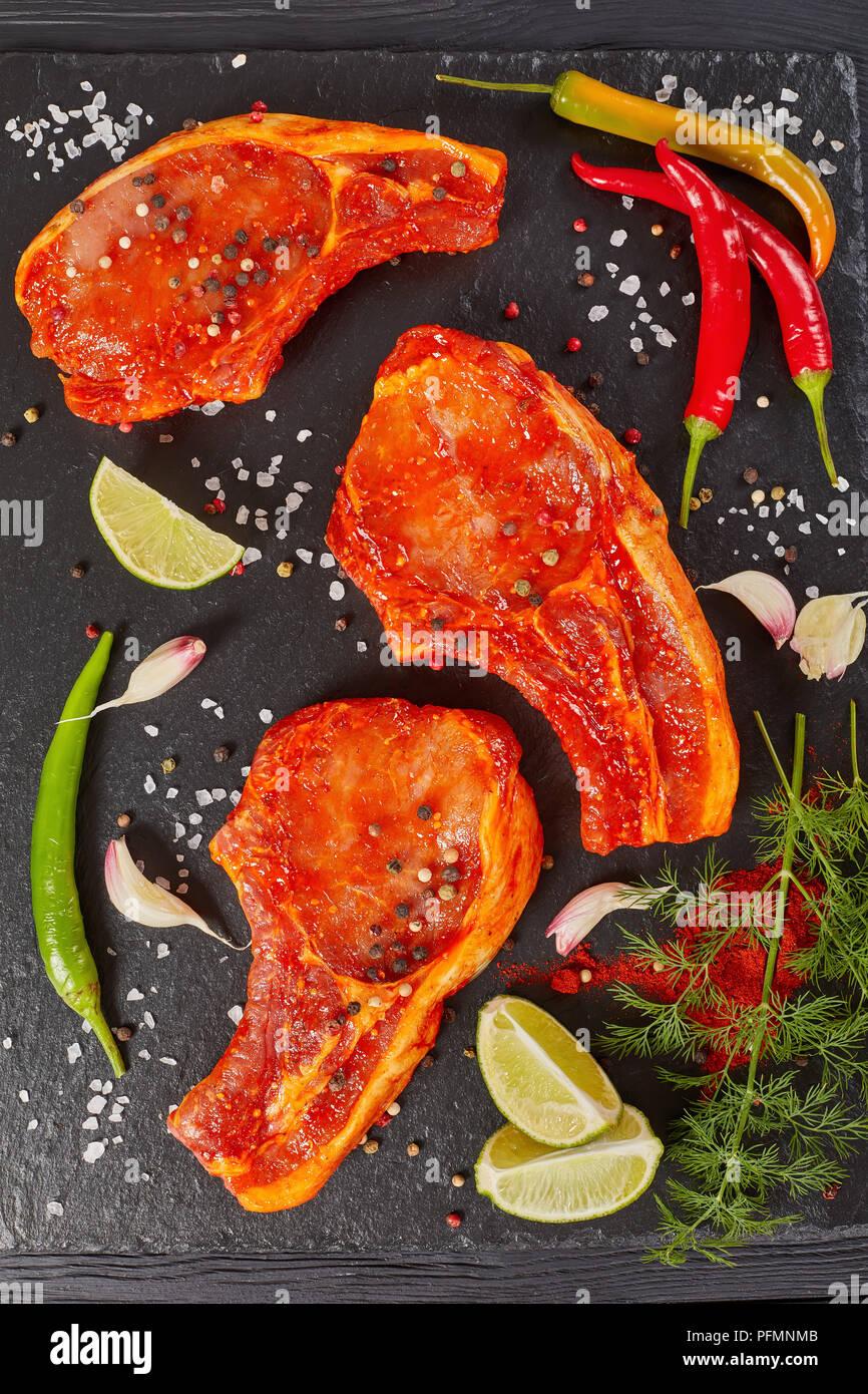Côtelettes de porc crus prêts à cuire, mariné aux épices et sauce sriracha rouge sur noir ardoise plateau avec piment, sel, épices et des tranches de lime, ver Photo Stock