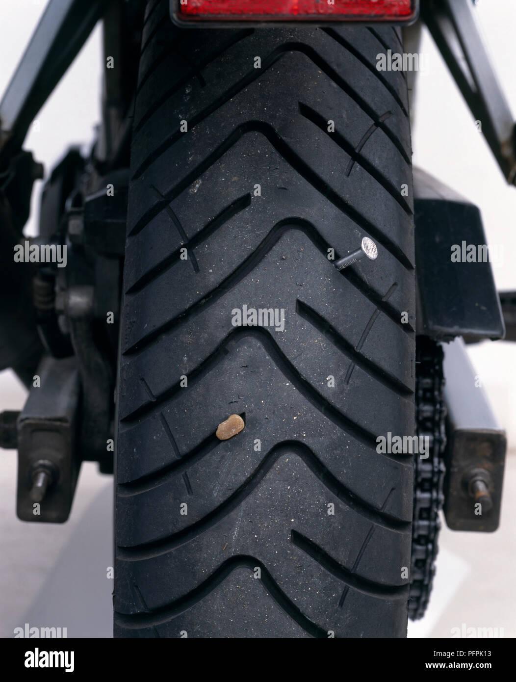 Close-up d'un clou et une pierre enchâssée dans la bande de roulement d'un pneu. Banque D'Images