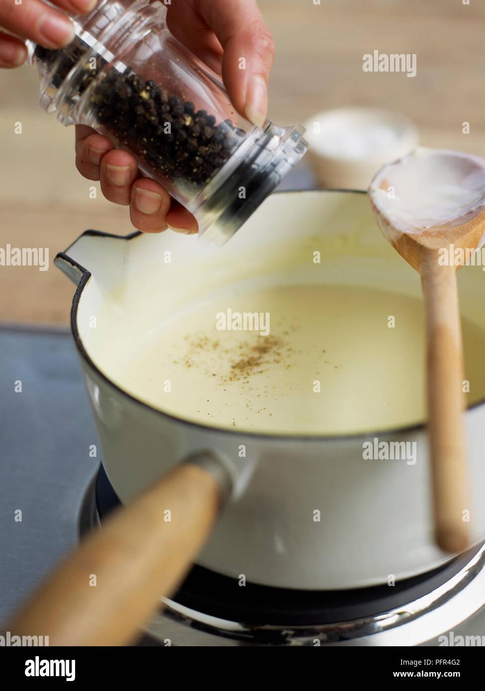 L'ajout de poivre sauce béchamel Banque D'Images