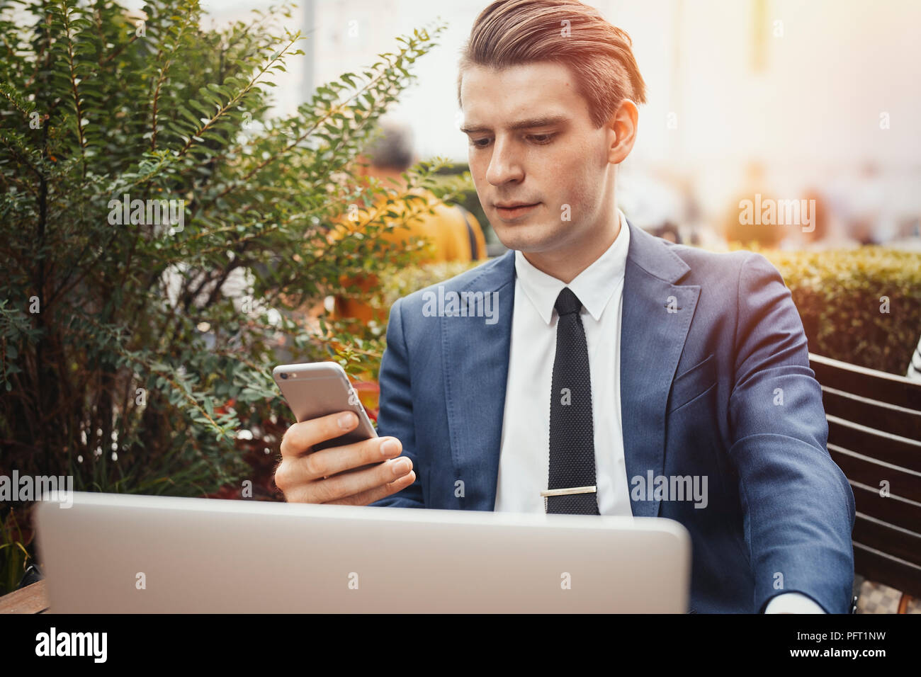 Young businessman holding mobile phone dans la main et assis à côté de l'ordinateur portable. Photo Stock