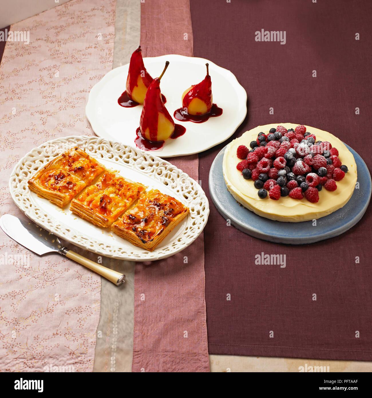 Collection de dessert, tarte aux abricots et amandes galette, confit de poires avec sauce citron cheesecake, surmontées de baies fraîches Photo Stock