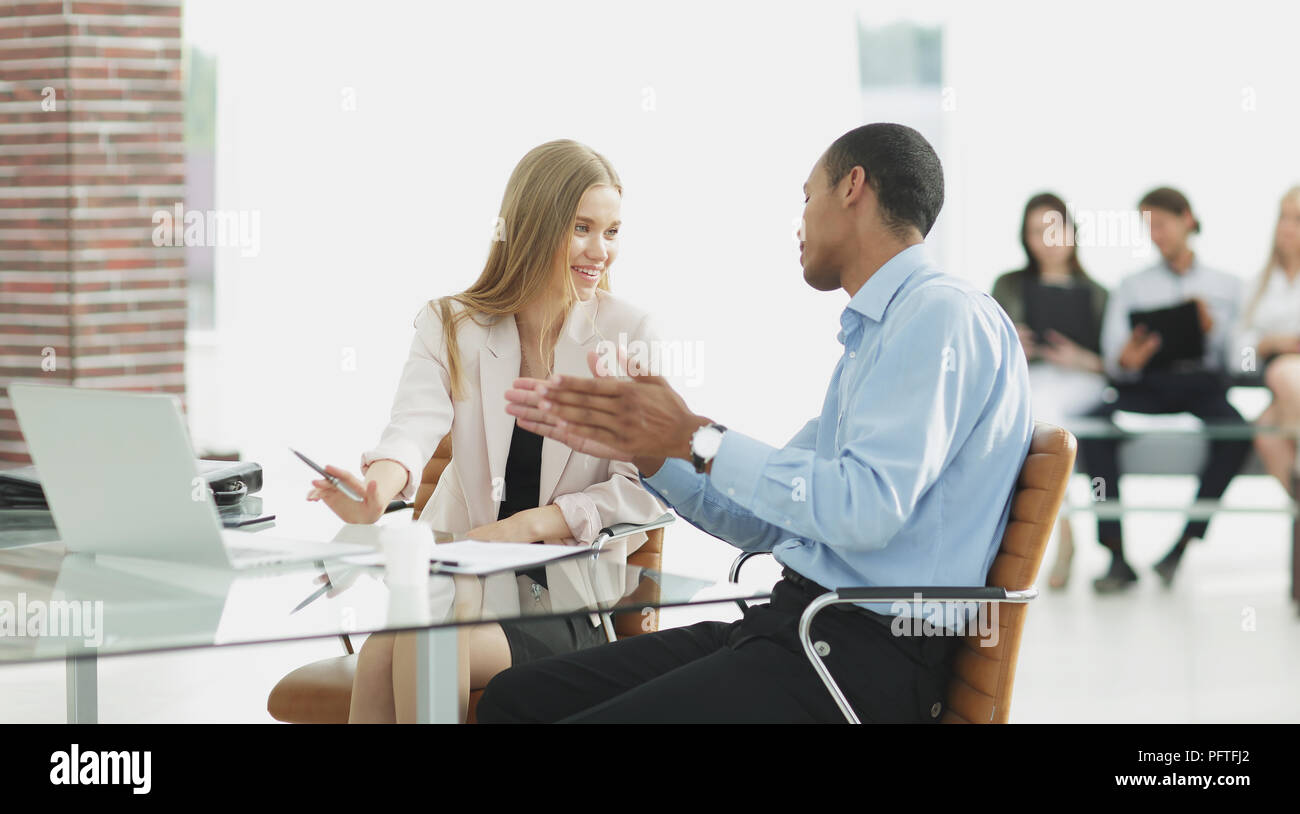 Les jeunes collègues d'affaires parler derrière un bureau Photo Stock