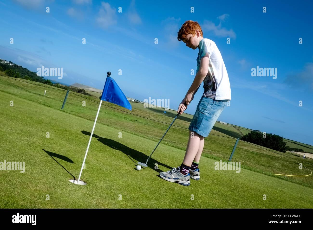 Jeune garçon adolescent pratique de mettre une balle de golf sur un green.Cornwall Polzeath. Banque D'Images