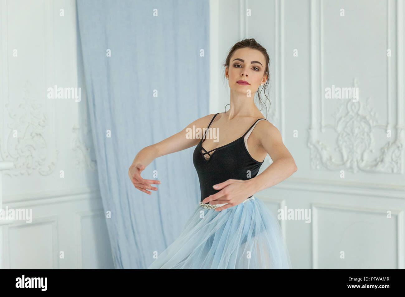 Jeune danseuse de ballet classique vue de côté. Belle ballerine ballet gracieux pratique des positions en tutu jupe près de grand miroir dans la salle de lumière blanche. B Photo Stock