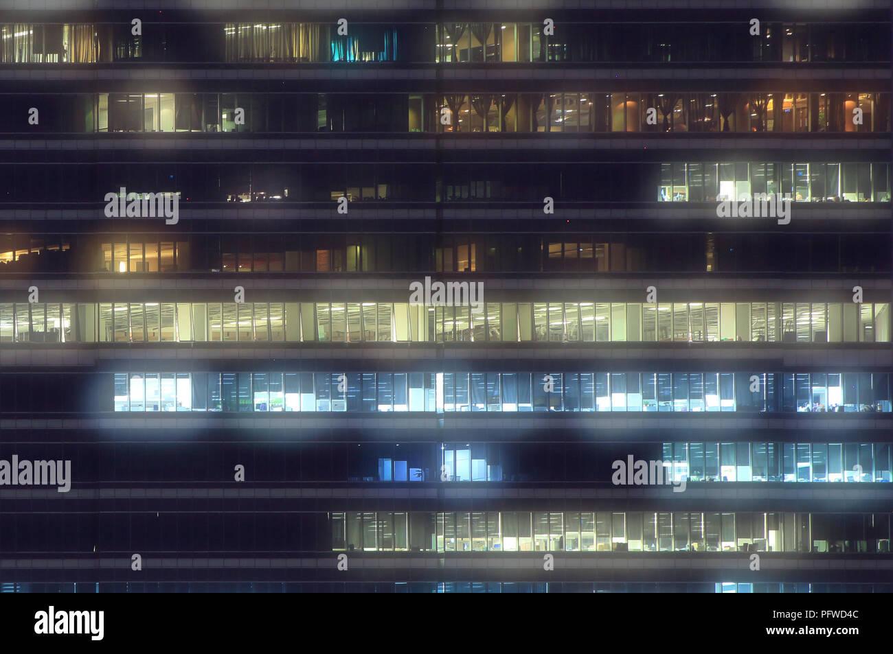 Les travailleurs d'un immeuble de bureaux. boîte de lumière la nuit. logement bâtiment moderne en verre et metal clad office building s'allumer le soir. Banque D'Images
