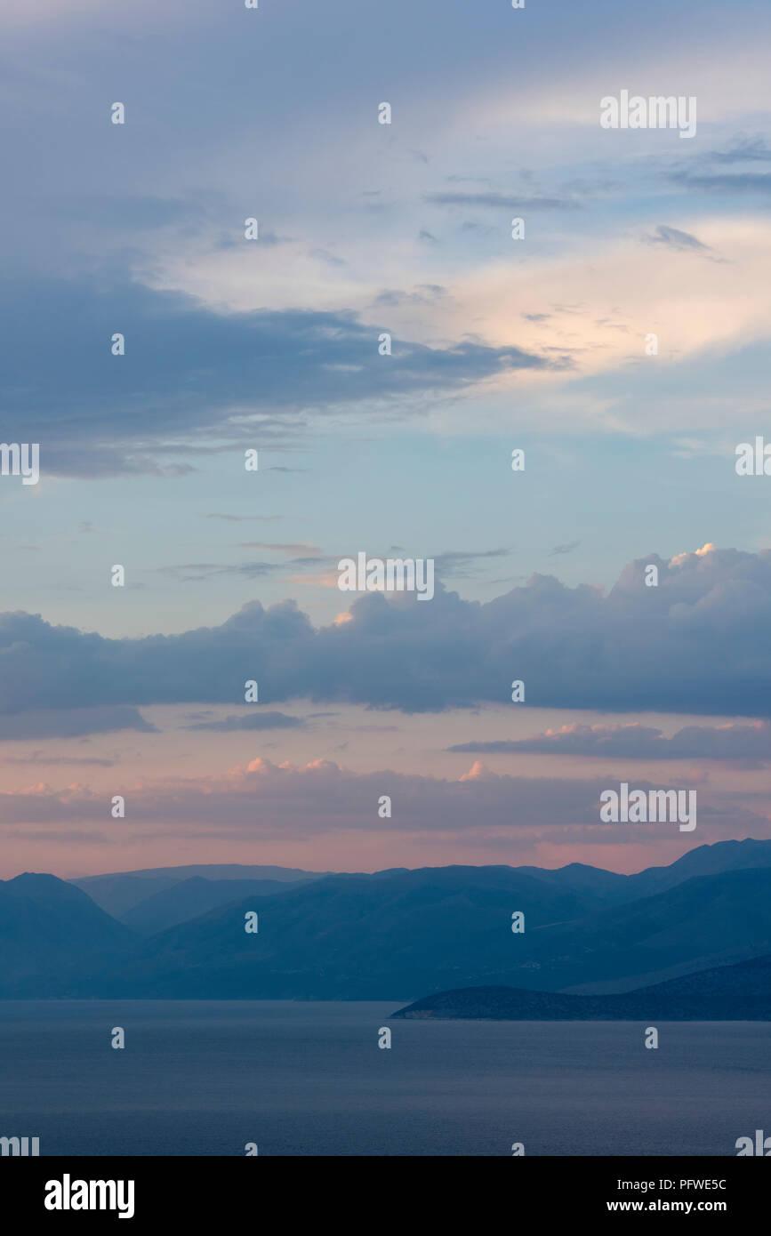 Coucher de soleil sur la côte albanaise et les montagnes vue depuis les collines au-dessus de kassiopi sur l'île grecque de Corfou. Photo Stock