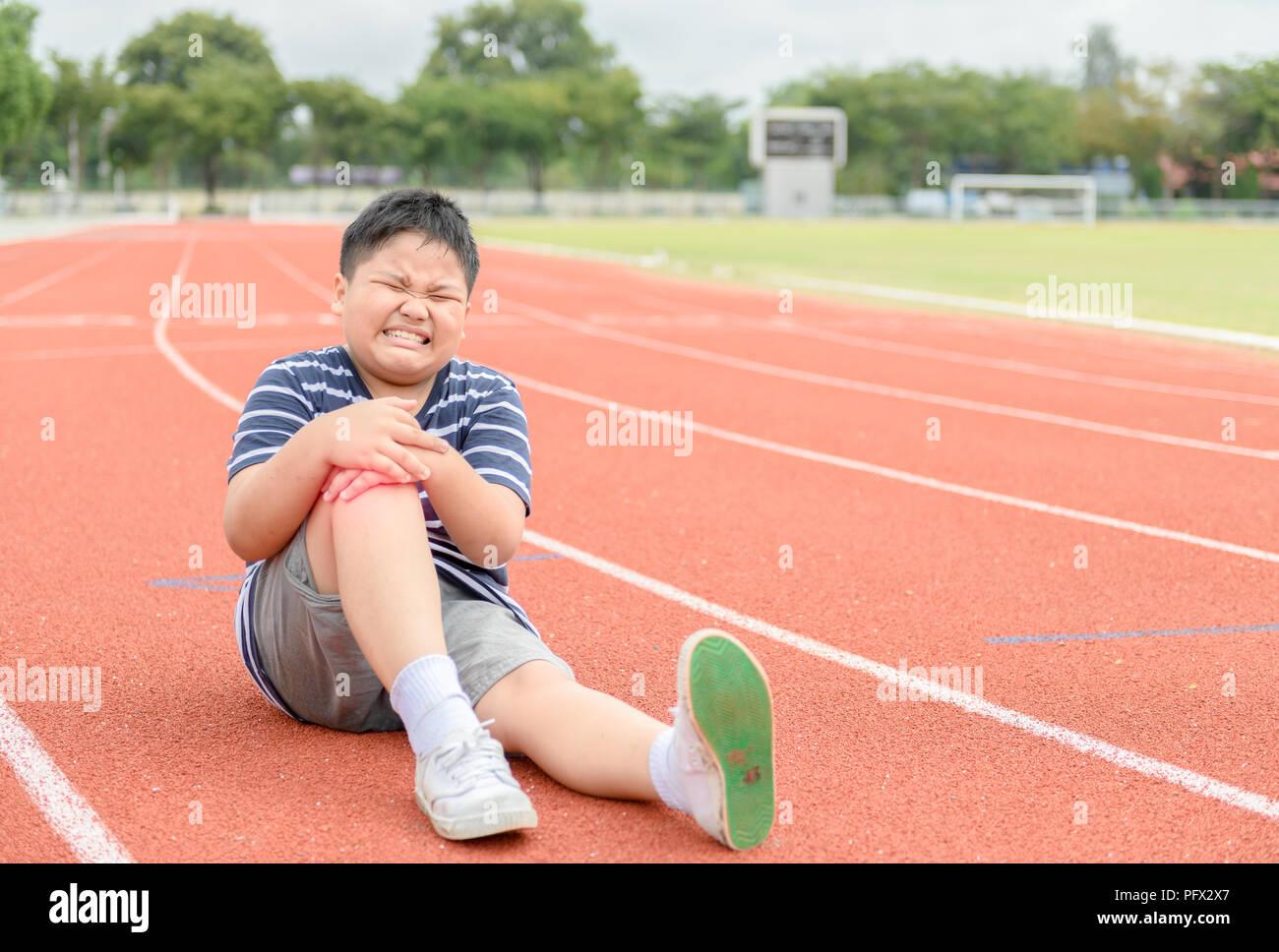 Garçon obèse la sensation de douleur après avoir blessé son genou sur la piste, l'exercice de sport concept de dommage Banque D'Images