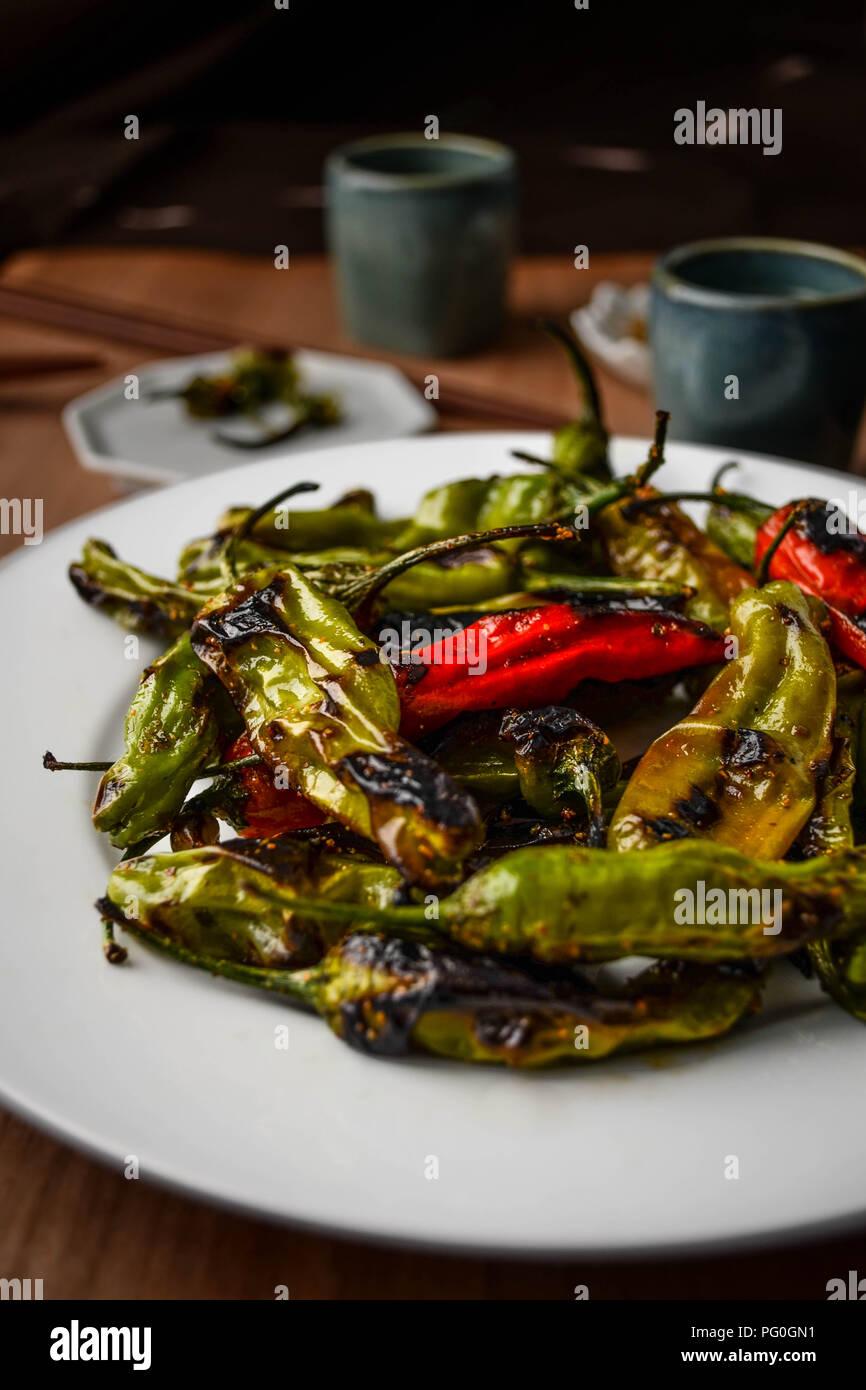 Vert et Rouge carbonisé shishito peppers avec sweet spice togarashi servi sur une plaque blanche ronde. Photo Stock