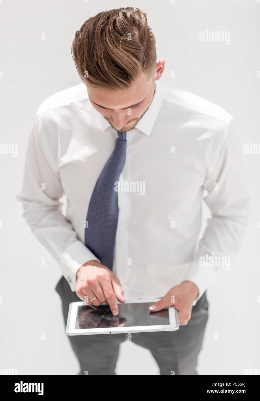 Homme confiant dans une chemise et cravate travaille sur une tablette numérique Banque D'Images