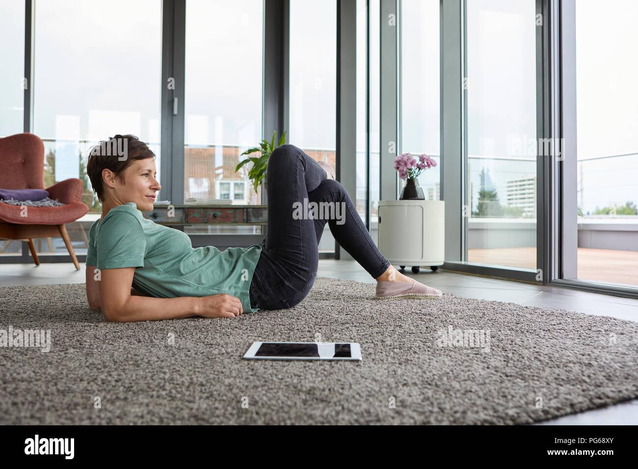 Femme allongée sur le sol à la maison avec tablet à la porte du balcon de Photo Stock
