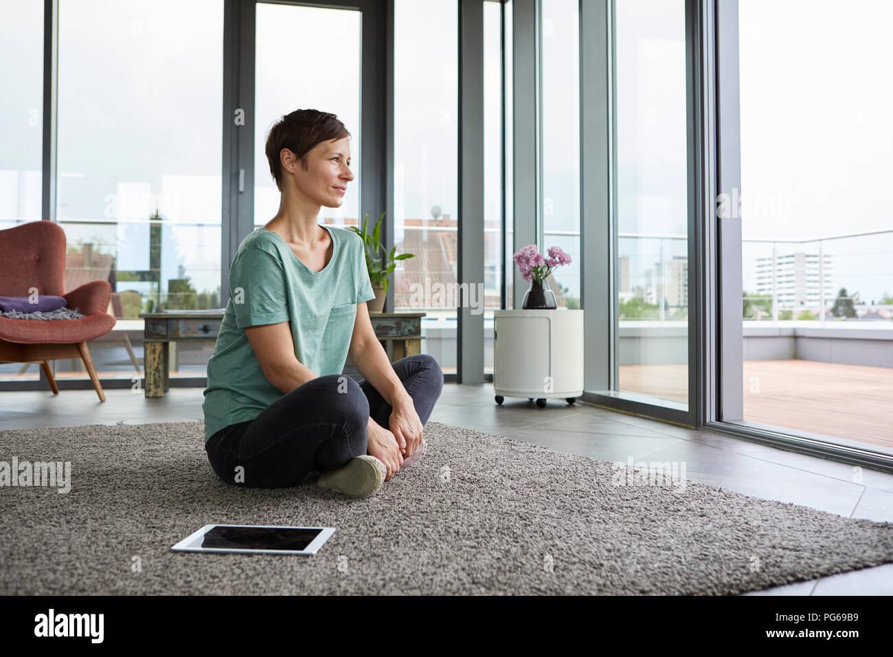 Femme assise sur le sol à la maison avec tablet à la porte du balcon de Photo Stock