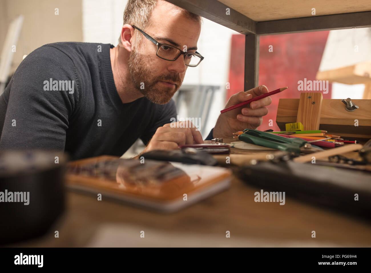L'homme dans un studio d'artiste contrôles des fournitures Photo Stock