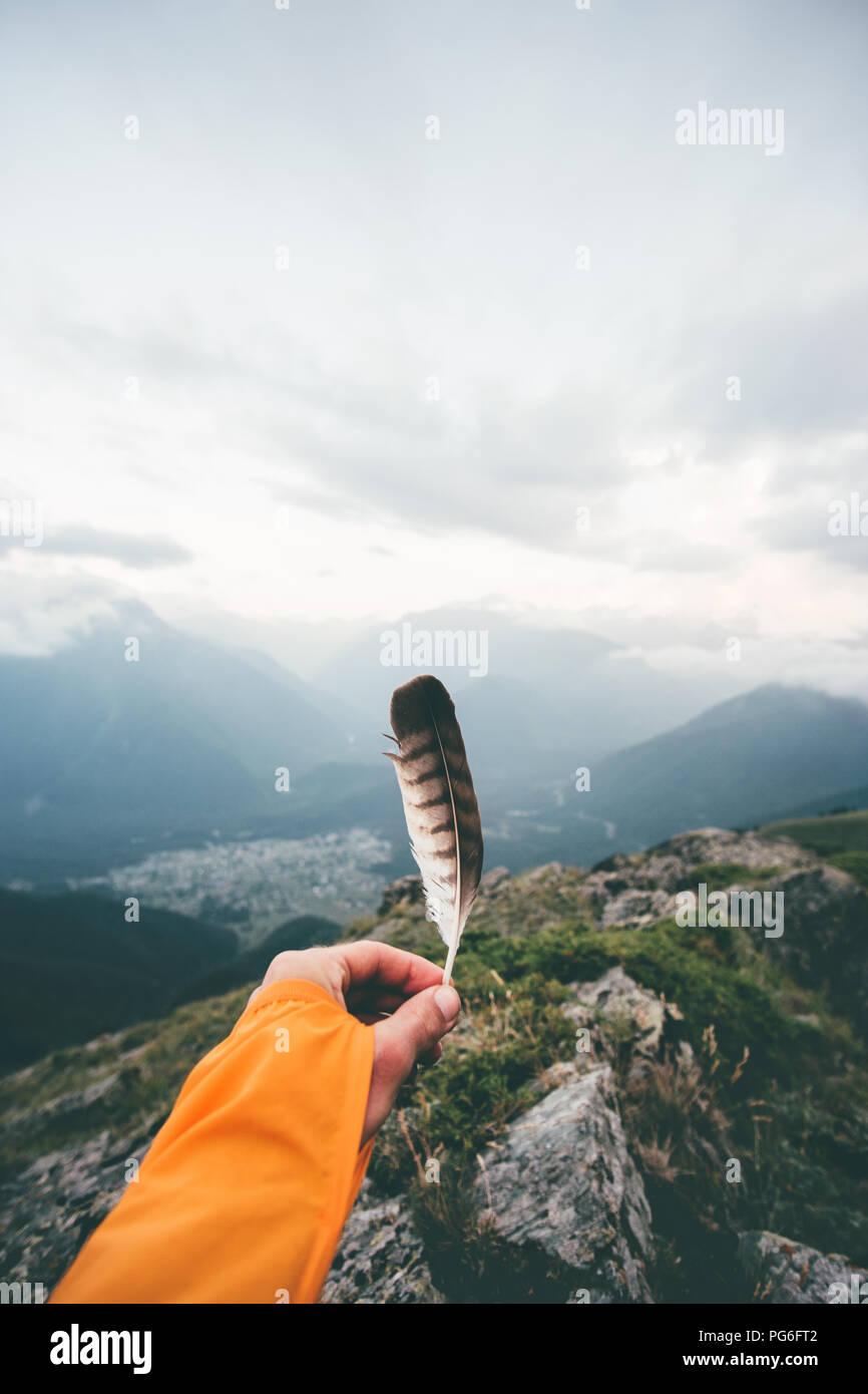 Hand holding bird feather moody vue aérienne paysage montagnes aventure voyage concept de vie la liberté et la solitude émotions l'harmonie avec la nature Photo Stock