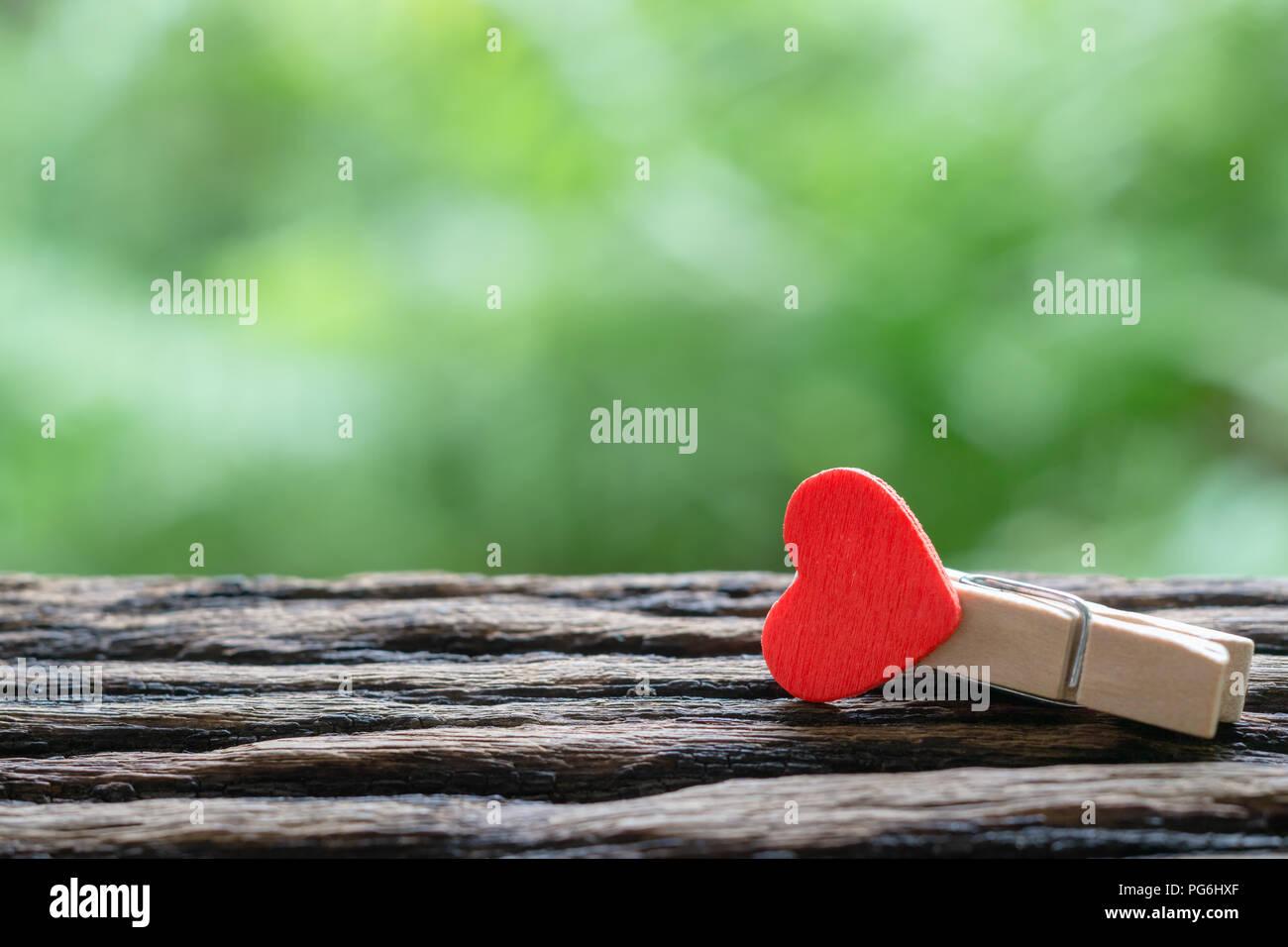 De gros plan en bois coeur rouge Trombones avec green nature fond et copier l'espace. Idéal pour la Saint-Valentin, l'amour et des relations Photo Stock