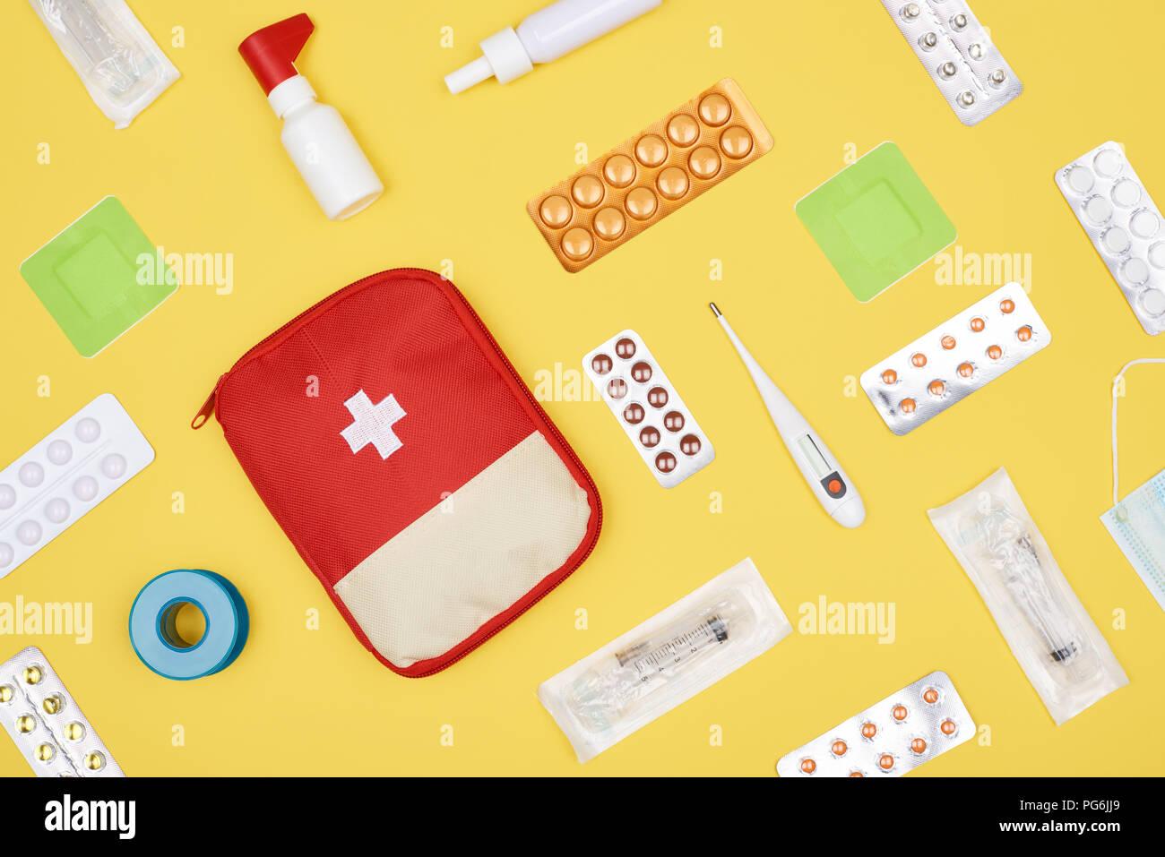 Vue de dessus de trousse de premiers soins avec différents médicaments isolé sur le jaune Banque D'Images