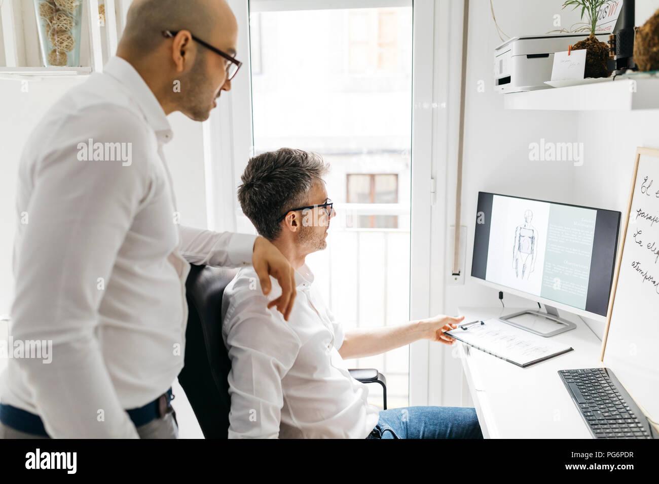 Deux collègues travaillant sur pc de bureau à la maison Photo Stock