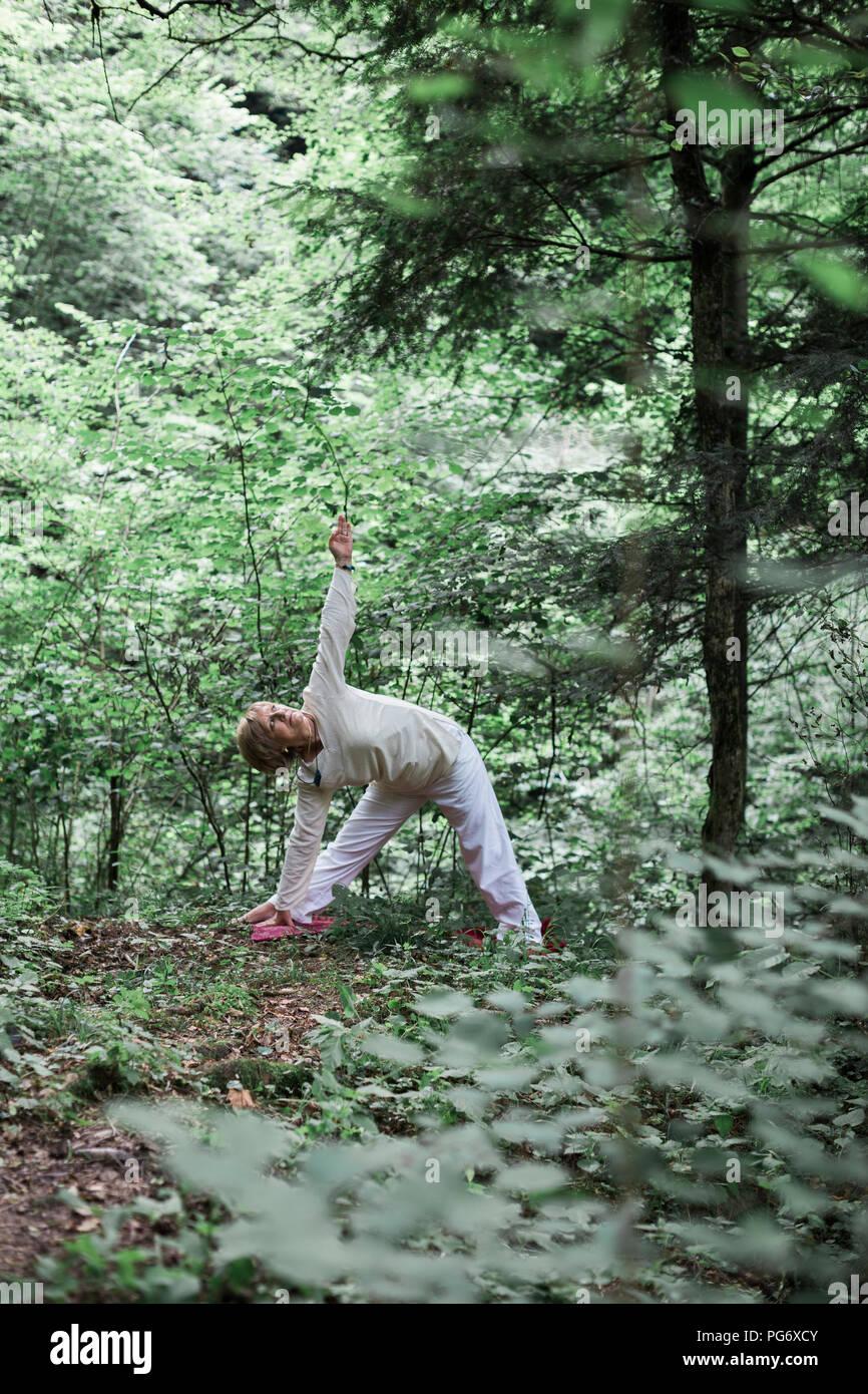 Senior woman doing yoga dans la forêt, triangle poser Photo Stock