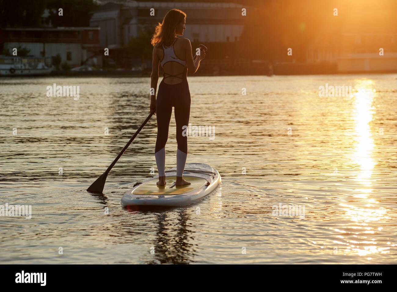 Stand Up Paddle board yoga effectué par belle fille sur la ville lumineuse, l'arrière-plan de formation de yoga sur la plage Photo Stock