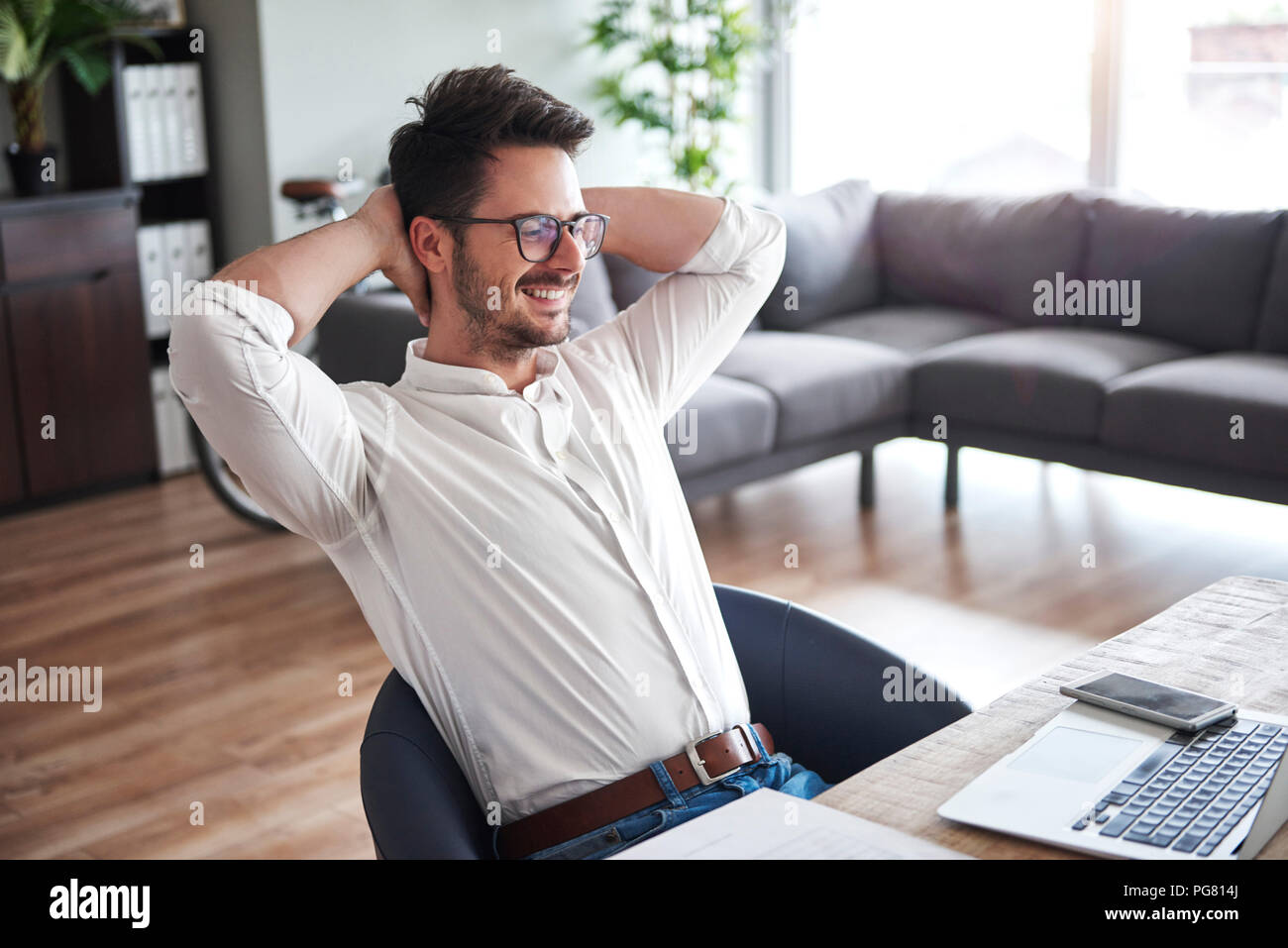 Content businessman sitting at desk at home office Photo Stock