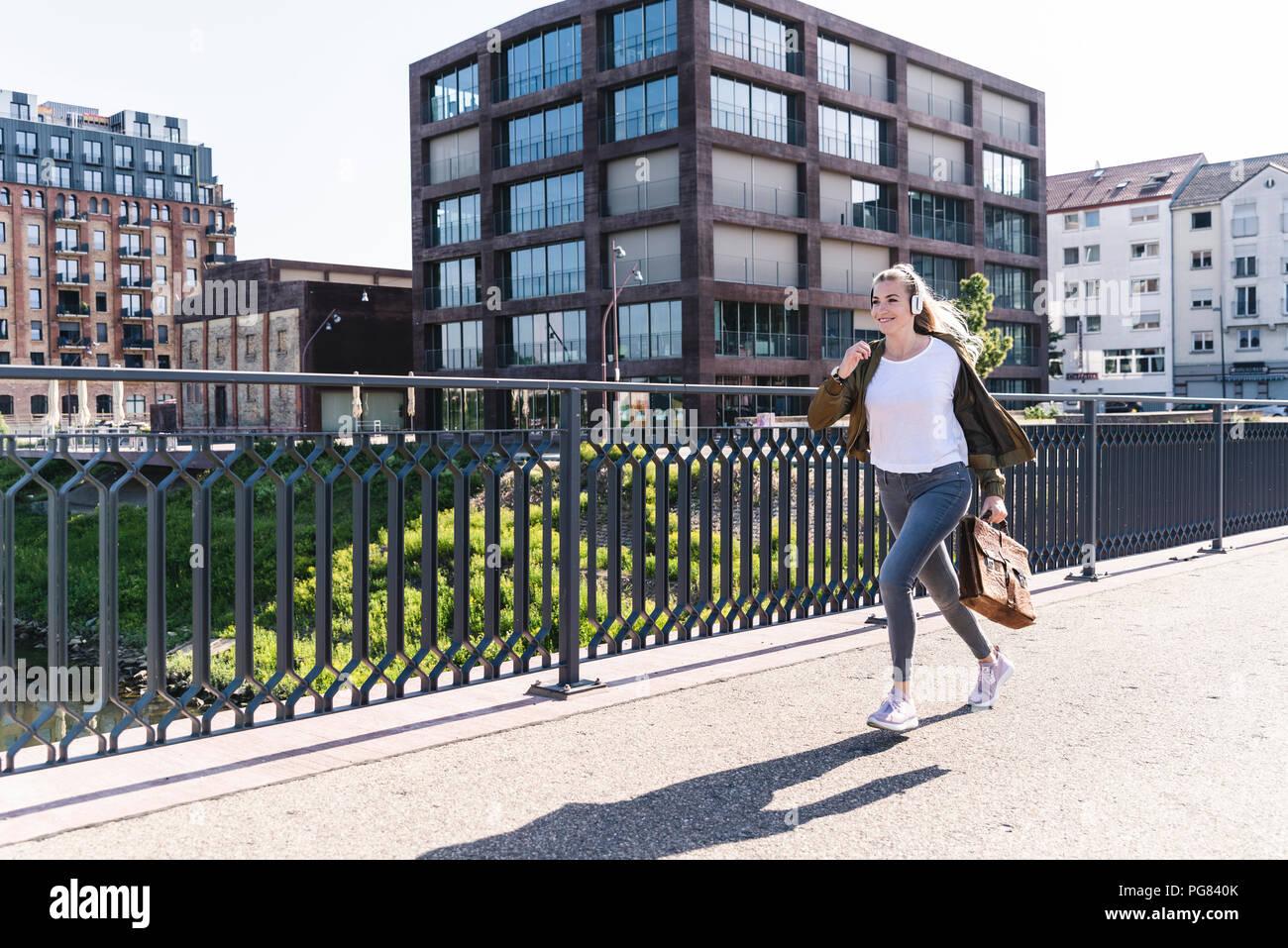 Jeune femme tournant sur le pont, à l'écoute de la musique avec des écouteurs Photo Stock