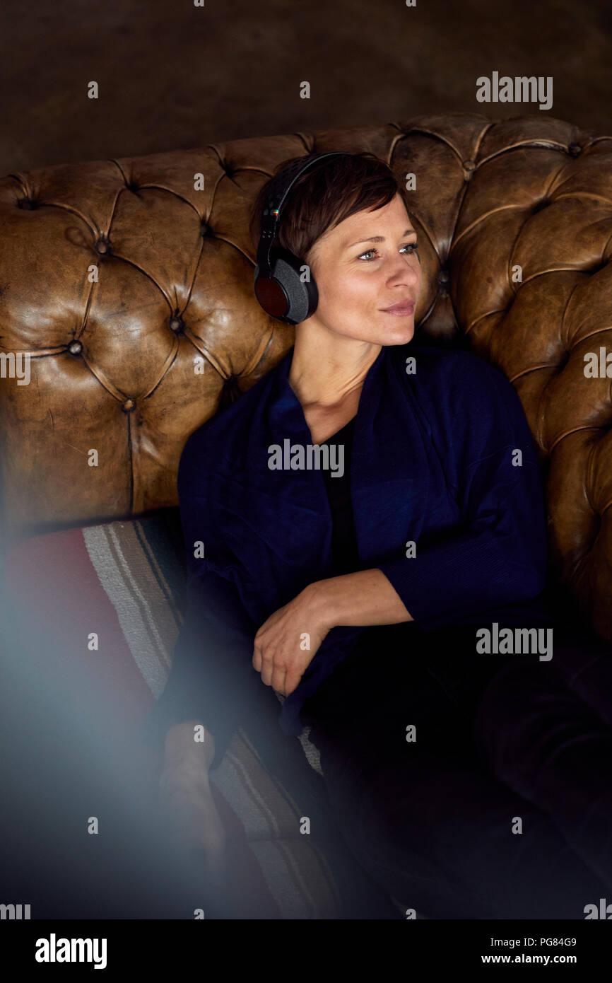 Femme avec casque allongé sur un canapé, écouter de la musique Photo Stock