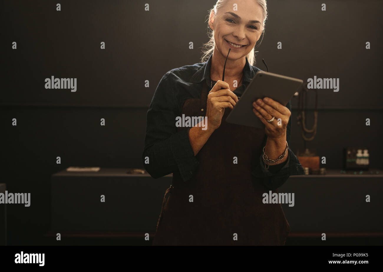 Portrait of smiling senior woman wearing apron holding digital tablet dans son atelier de joaillerie. Smiling mature femme goldsmith avec tablette PC. Photo Stock