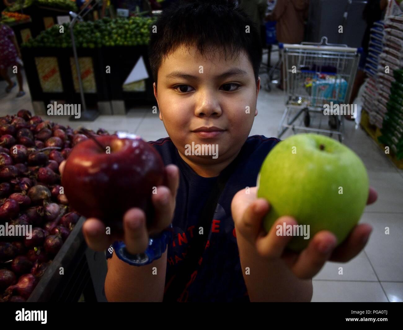 Photo d'un jeune garçon asiatique montre une pomme verte et rouge à l'intérieur d'un supermarché. Photo Stock