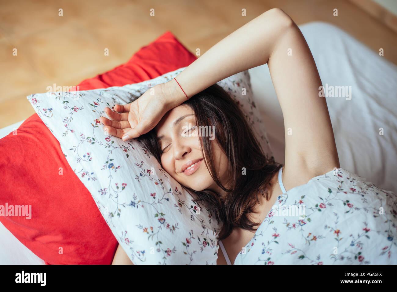Young woman smiling tout en dormant dans son lit à la maison. Relax concept Photo Stock