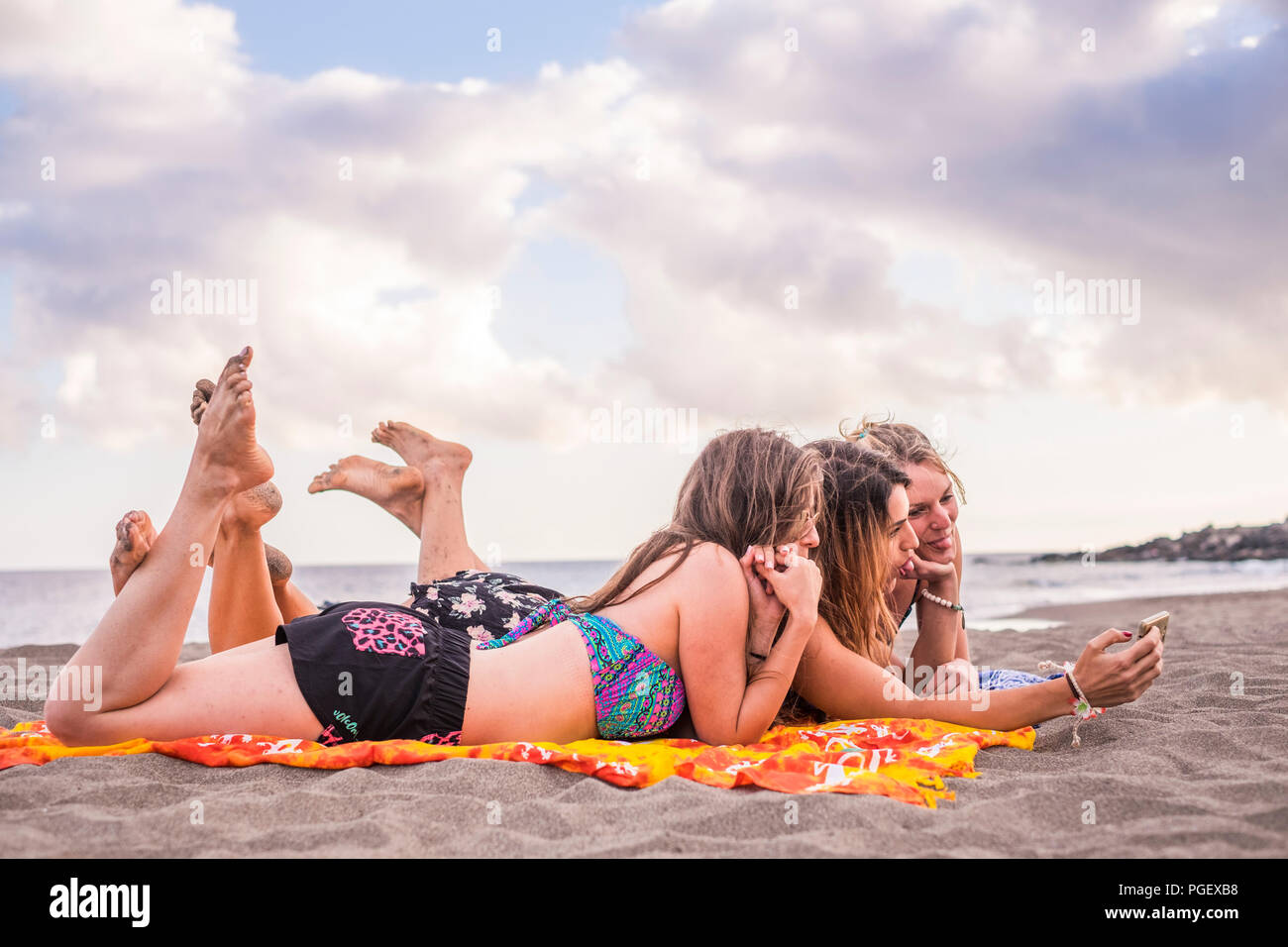 L'été, vacances, congés, de la technologie et de bonheur concept - group of smiling people with sunglasses taking picture with smartphone sur plage. happin Photo Stock