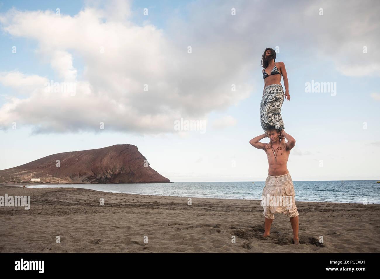 Position acrobatique balnced pour belle brave couple homme et femme jeunes debout à un de l'autre à la plage de l'océan avec en arrière-plan. extr Photo Stock