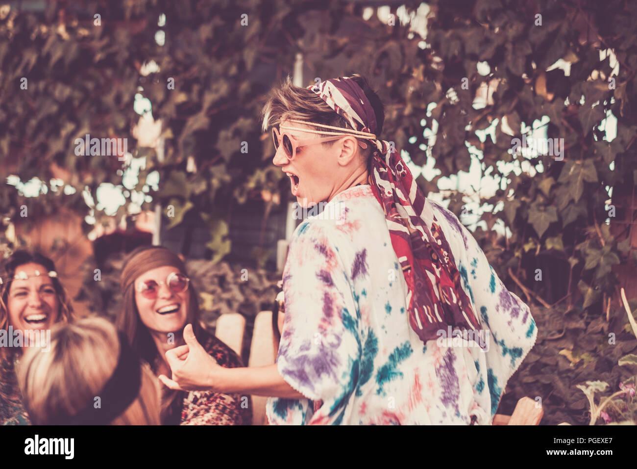 Jeune femme blonde crazy et les filles dans l'amitié tous ensemble célébrer et s'amuser dans un lieu naturel bio. sourires et rires pour groupe d'Hipp Photo Stock