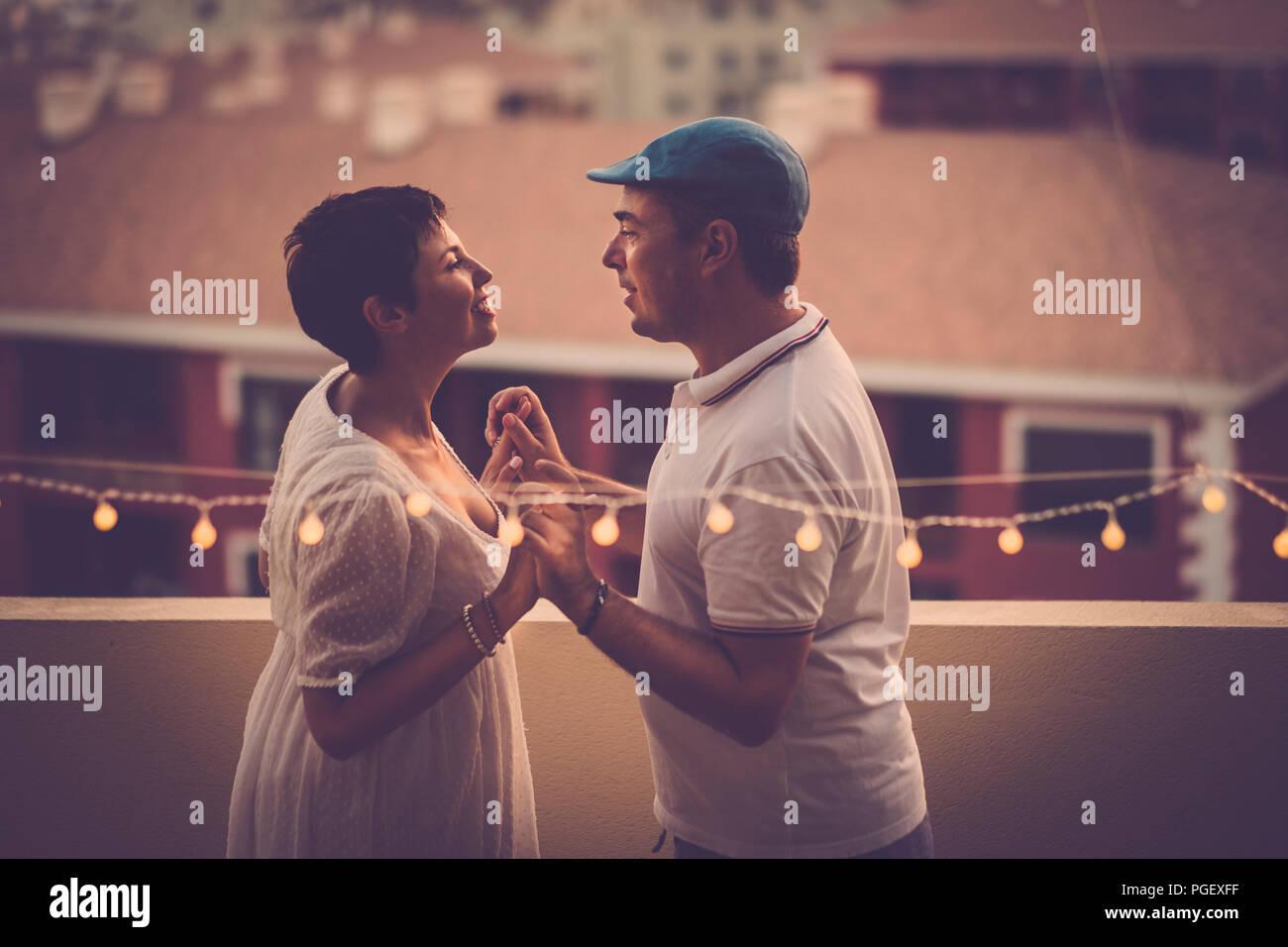 Beau moyen age couple in love smiling eachother et à la recherche dans les yeux à la terrasse avec une vue de dessus. houese relation Photo Stock