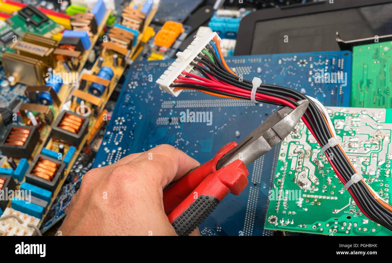L'élimination des déchets électroniques. La main avec une pince. Câbles d'alimentation avec connecteur pour carte mère d'ordinateur. Circuits imprimés, pièces PC électrique sur fond coloré. Photo Stock