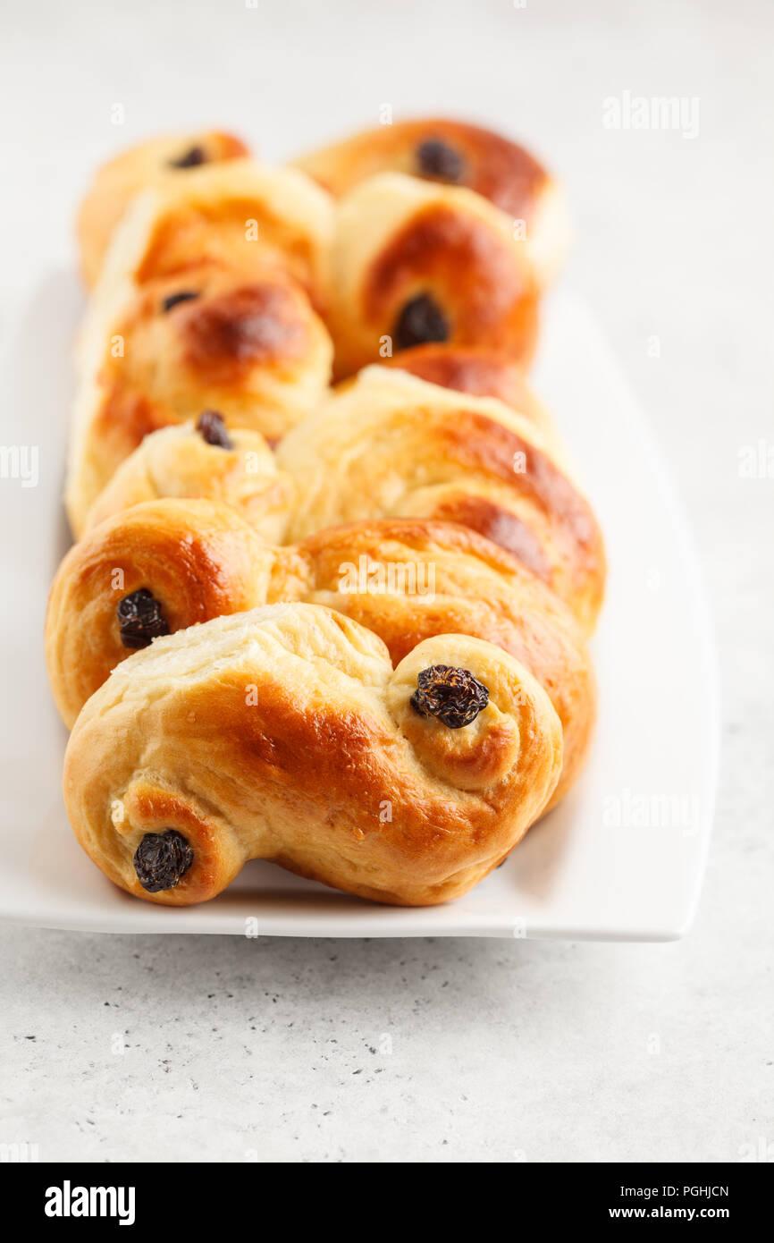 Petits pains au safran traditionnel suédois (lussebulle ou lussekatt), fond blanc, petit déjeuner européen. Banque D'Images