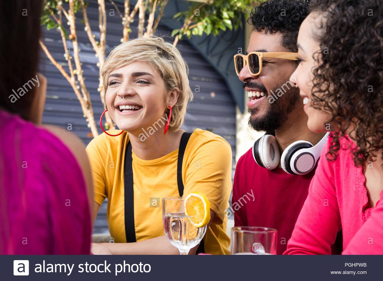 Les jeunes adultes sortir, s'amuser au restaurant à l'extérieur. Les étudiants multiculturels fête ensemble au cafe bar piscine. Printemps, accueil chaleureux, convivialité, Photo Stock