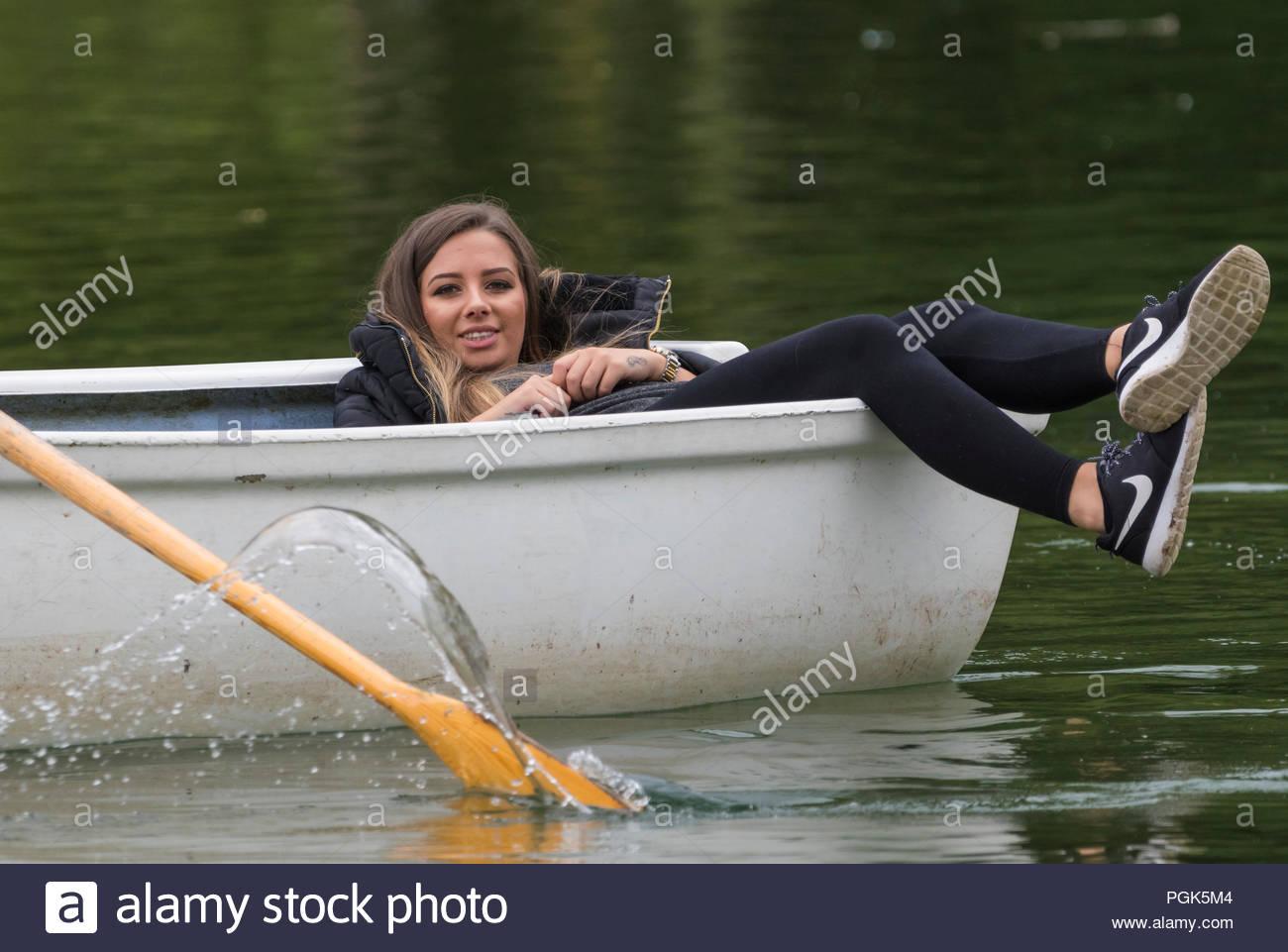 Une jeune femme portant retour relaxant dans un bateau à rames à un lac de plaisance dans le lac Départment, Arundel, West Sussex, Angleterre, Royaume-Uni. Photo Stock